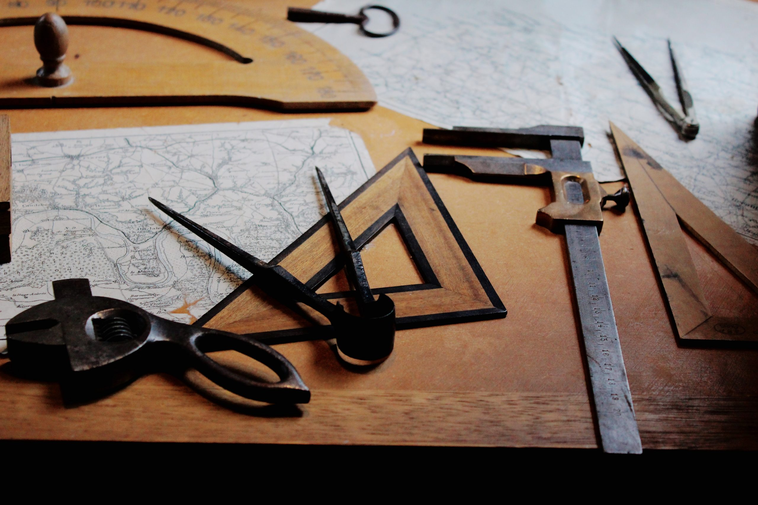 Ruler, compass and other measurement tools displayed on a desk.