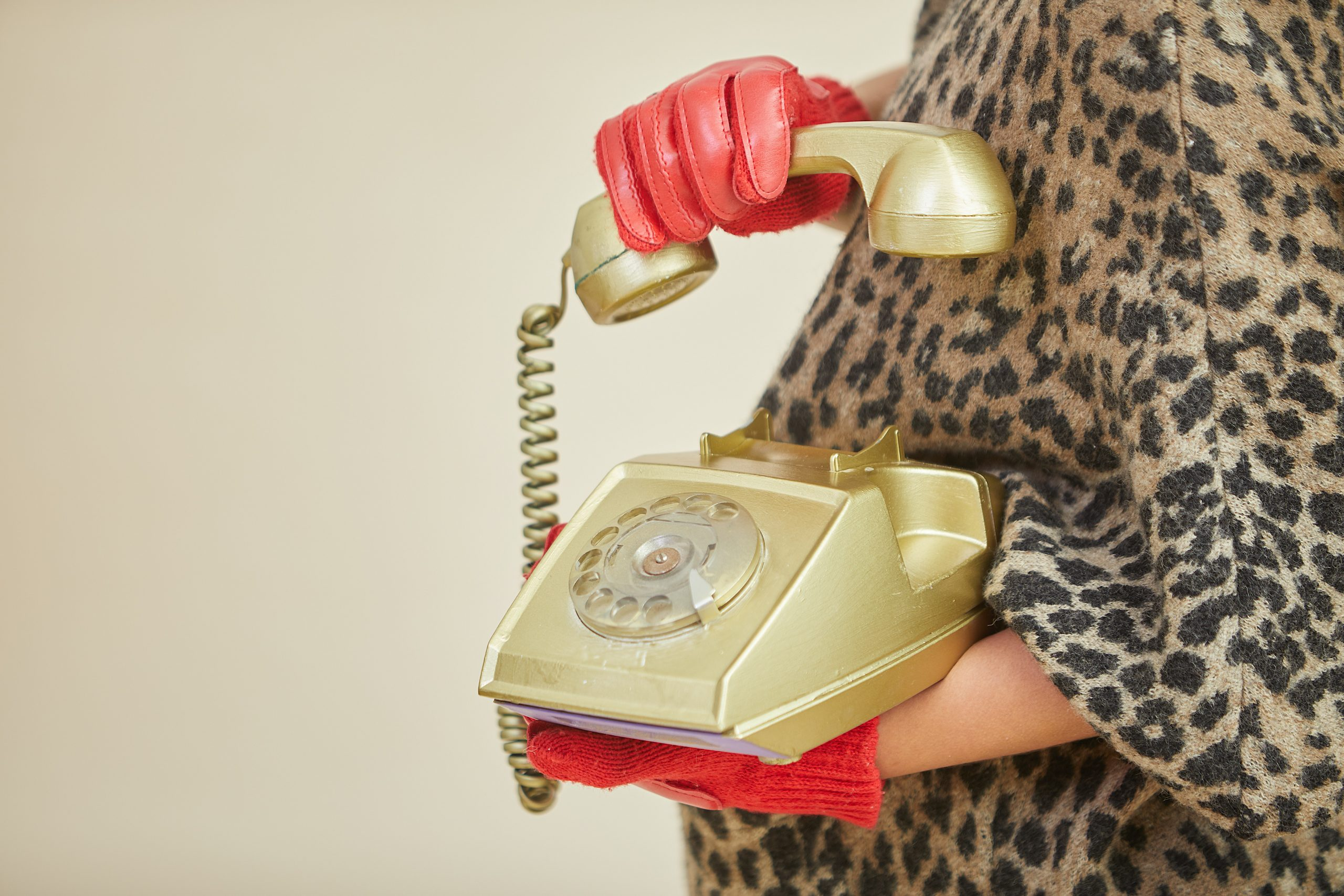 Woman with red gloves holding rotary phone.