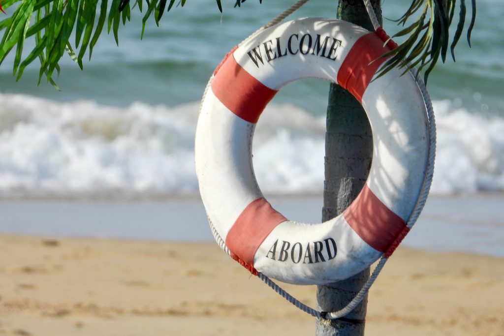 Welcome aboard life saver hanging on a palm tree on the beach.
