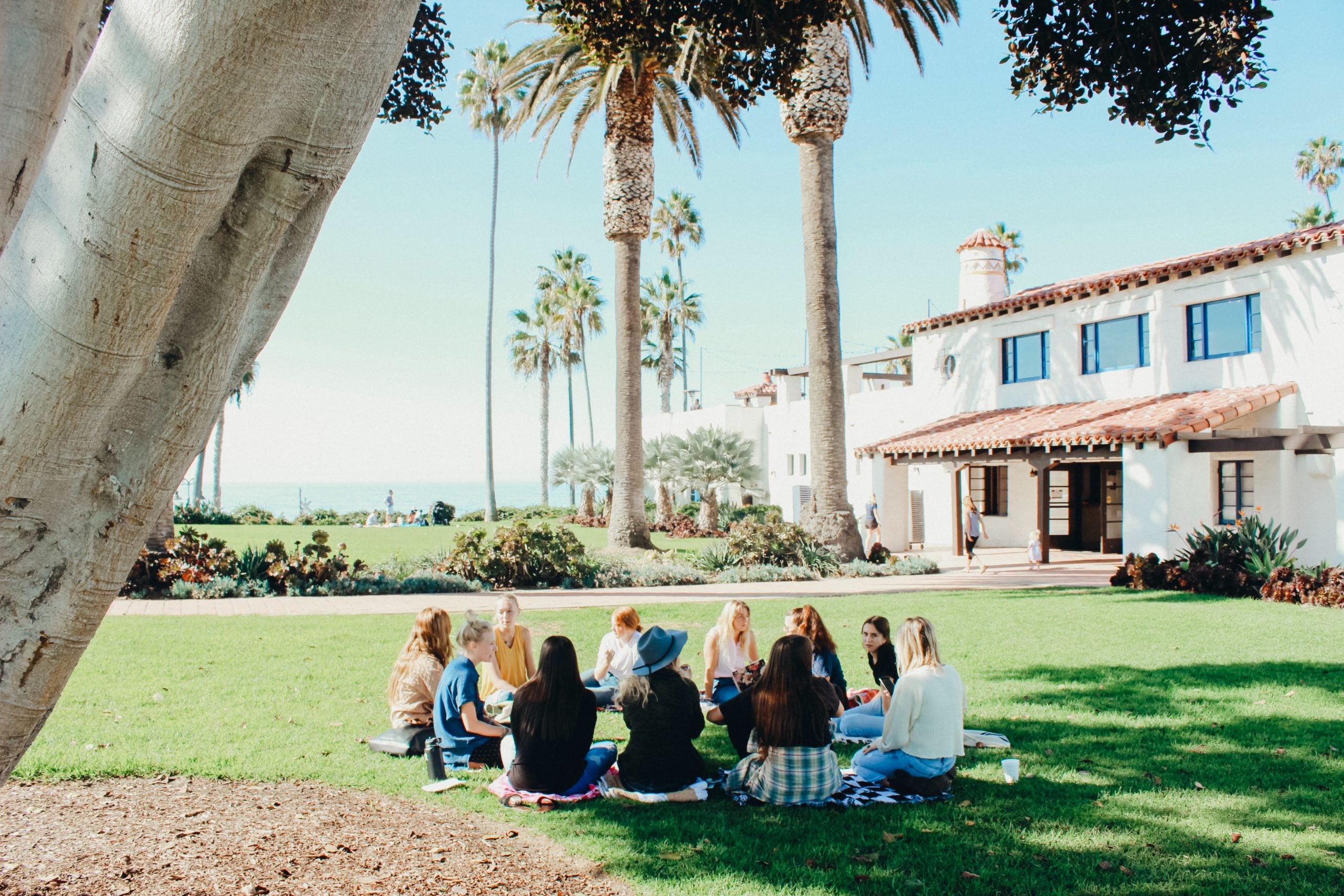 Students sitting in a circle on the lawn.