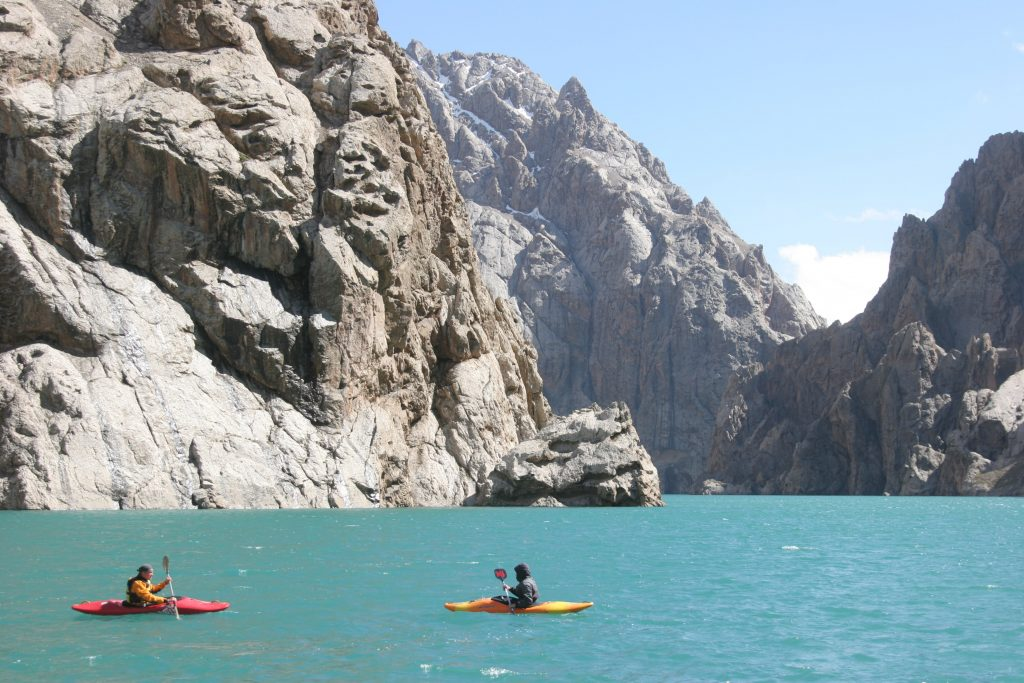Kayakers on an alpine lake surrounded by rocky mountains.