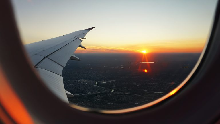 View of sunset and plane wing from plane window.