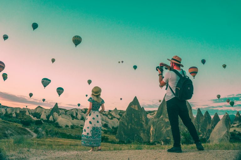Woman being photographed in front of hundreds of hot air balloons.